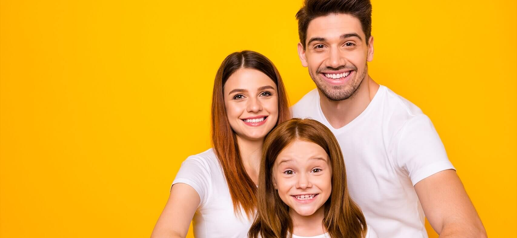 Family of three smiling in front of a yellow background