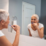 Woman with short white hair sticks to her oral hygiene routine and brushes her teeth