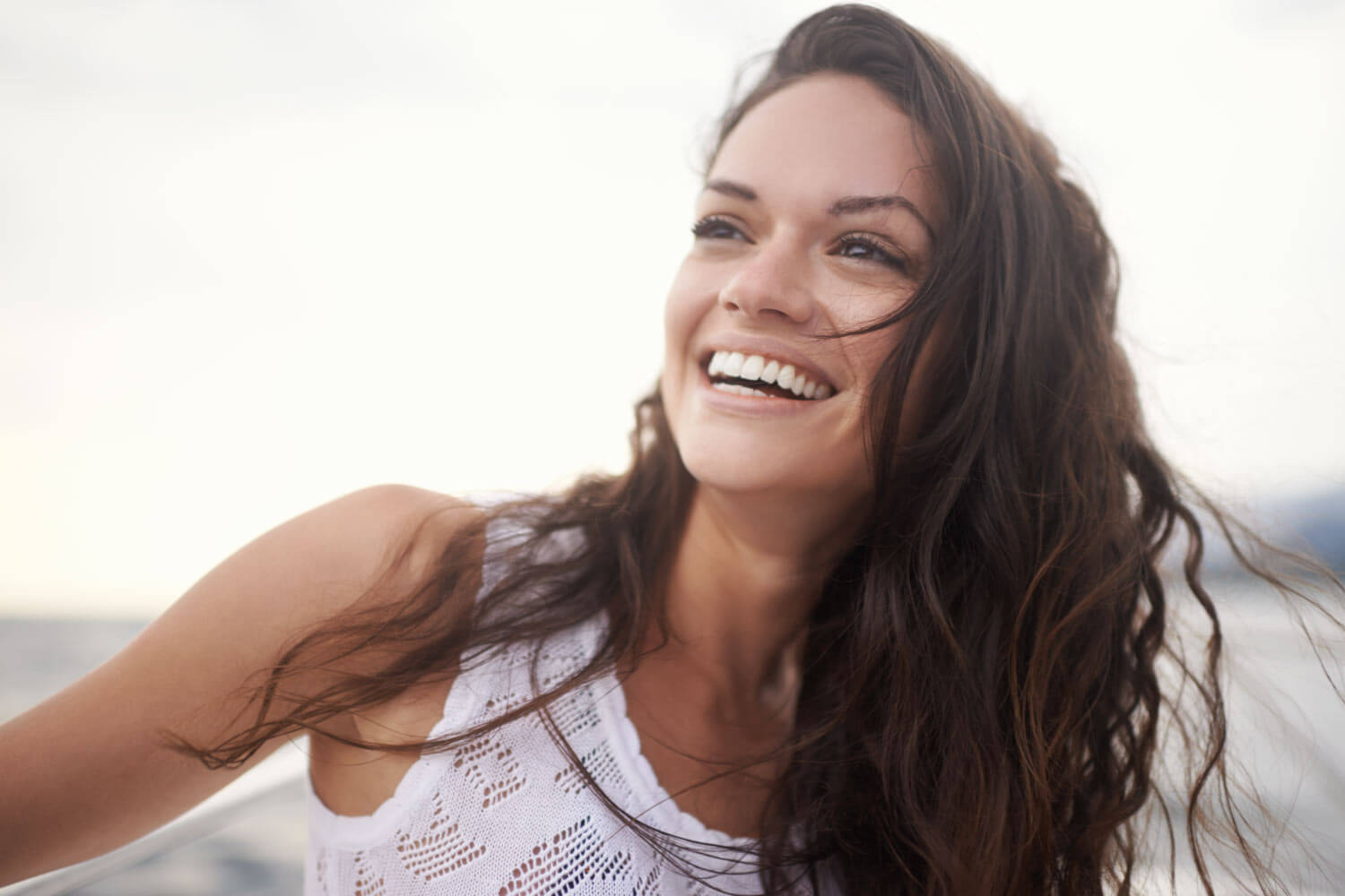 Brunette woman smiles after getting cosmetic dentistry in Wolcott, CT