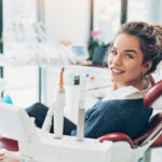 Brunette woman in a dental chair smiles while at her dentist in Wolcott, CT